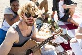 Handsome young man in sunglasses playing guitar and looking at camera while chilling with friends du poster