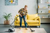 Beautiful Woman Cleaning Carpet With Vacuum Cleaner At Home poster