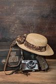 Travel Concept With Vintage Suitcase, Wicker Hat And Old Camera A Dark Wooden Grunge Background With poster