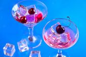 Cherry Drink In Cocktail Glasses With Ice Cubes On A Blue Background. Refreshing Cold Drink With Cop poster
