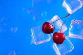 Fresh Cherries On A Stack Of Ice Cubes Close-up On A Bright Blue Background. Refreshing Summer Bever poster