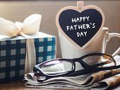 Happy Fathers Day Concept. Coffee Cup With Gift Box, Heart Tag With Happy Fathers Day Text And News poster