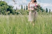 Cropped Shot Of Woman Holding Bouquet Of Flowers While Standing In Field Alone poster