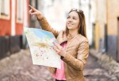 Tourist With Map In The City. Woman Pointing At Right Direction Or Showing Attraction With Finger. H poster