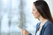Sad Woman Holding A Smart Phone And Looking Through A Window In A Rainy Day poster