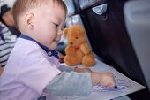 Little Asian 1 Year Old Toddler Boy Coloring In Coloring Book With Crayons During Flight On Airplane poster