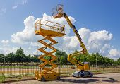Yellow Self Propelled Articulated Boom Lift And Scissor Lift On Background Of Street With Trees And  poster