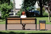 Redhead Girl Sitting On Bench In City Park And Talking On Phone. Young Woman With Red Hairs Sitting  poster