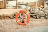Safety On The Beach. Boy Child Playing With Life Saver. Baby Care And Childhood Concept. Happiness A poster