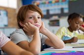 Tired school boy with hand on face sitting at desk in classroom. Bored schoolchild sitting at desk w poster