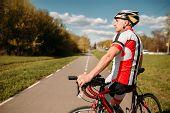 Cyclist in sportswear, cycling on asphalt road poster