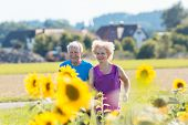 Cheerful senior couple with a healthy lifestyle jogging together side by side outdoors in the countr poster