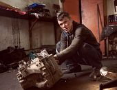 Auto Mechanic Squatting Working On Car Detail On Floor At Auto Repair Shop, Looking To The Camera. S poster