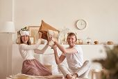 Pair In Love Laughing And Playing On Bed. Man And Woman Fight Pillows. Young Happy Couple Beat The P poster
