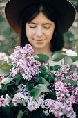Big Lilac Flowers Bouquet In Hands Of Stylish Boho Woman In Hat In Sunny Spring Park. Calm Portrait  poster
