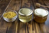 Different Varieties Of Honey In Small Glass Jars And Bee Pollen On The  Brown Wooden Background. Clo poster