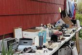 stock photo of yard sale  - Variety of old unwanted objects on two tables near a wall of a house in a driveway being displayed for sale at a yard sale - JPG