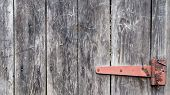 Old Wooden Background With A Rusty Hinge. Antique Door Hinges. Red Metal Hinge On Gray Wood Close Up poster
