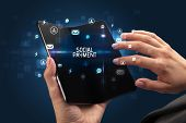 Businessman holding a foldable smartphone with SOCIAL PAYMENT inscription, social networking concept poster