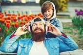 Happy Family Listen Music With Wireless Headphones Outdoors. Stylish Father And Son Spending Time To poster