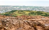 Landscape Of Edinburgh City In Scotland Viewed From Arthurs Seat In Overcast Weather With Red Rocks  poster