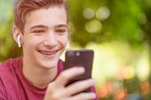 Happy teenage boy is using mobile phone, outdoors.  Close-up portrait of a smiling young man with sm poster