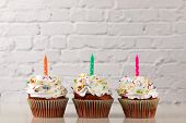 Cupcake. Delicious Cupcakes With Sprinkled Frosting And Candles On White Background, Copy Space poster