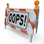 The word Oops on a construction barricade to warn of a mistake or error causing a problem, trouble o