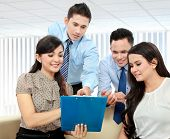 stock photo of employee month  - Portrait of successful business team discussing a monthly report - JPG