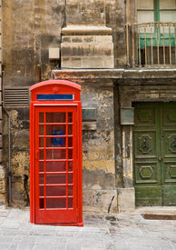 stock photo of phone-booth  - Old style red phone booth on a street in Valletta in the European country of Malta along the Mediterranean - JPG