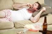 Unemployed middle aged man at home on the couch in his underwear, eating a hamburger,  with a mariju
