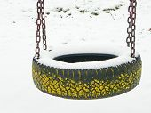 image of tire swing  - snowy tire swing on the empty playground in winter - JPG