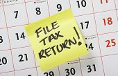 stock photo of self assessment  - Hand written reminder to File Tax Return on a yellow Post it Note stuck to a calendar background - JPG