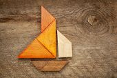 foto of tangram  - abstract picture of a sailing boat built from seven tangram wooden pieces over a rustic  barn wood - JPG