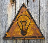 Light Bulb Icon on Rusty Warning Sign.