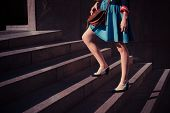 picture of up-skirt  - A young woman is walking up some stairs outside on a sunny day in the city - JPG