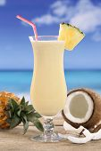 stock photo of pina-colada  - Cold Pina Colada cocktail with fruits on the beach while on vacation - JPG