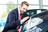 stock photo of showrooms  - Seller or car salesman in car dealership presenting the reflecting car paint of his new and used cars in the showroom - JPG