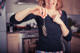 stock photo of field mouse  - A disgusted young woman is holding a dead mouse by it