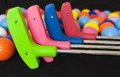 picture of miniature golf  - Four colorful mini golf putters with and assortment of balls - JPG