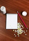 pic of prescription pad  - Writing Pad and the Pills on the Wooden Table closeup - JPG
