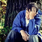 image of sorrow  - Toned photo of Sorrowful Teenager sitting in the Forest alone - JPG