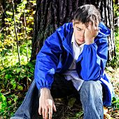 image of sorrow  - Sorrowful Teenager sitting under Tree in the Forest - JPG
