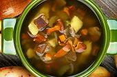 foto of chanterelle mushroom  - Delicious Vegetarian Soup with Chanterelle Mushrooms in Green Pot with Potato Onion Carrot closeup - JPG