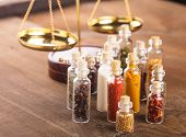 pic of vedic  - Little bottles with spices and scales on the table  - JPG