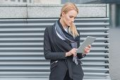 image of louvers  - Attractive stylish young blond woman standing using a tablet outdoors in front of a metal louver grating - JPG