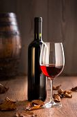 stock photo of merlot  - Red wine in wineglass and bottle with vintage barrel and fallen leaves.