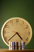 picture of analog clock  - Photo of an analog clock and rolls of paper money  - JPG