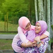 image of southeast asian  - Happy Southeast Asian Muslim mother and daughter at outdoor park - JPG