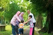 pic of southeast asian  - Happy family playing at outdoor garden park - JPG